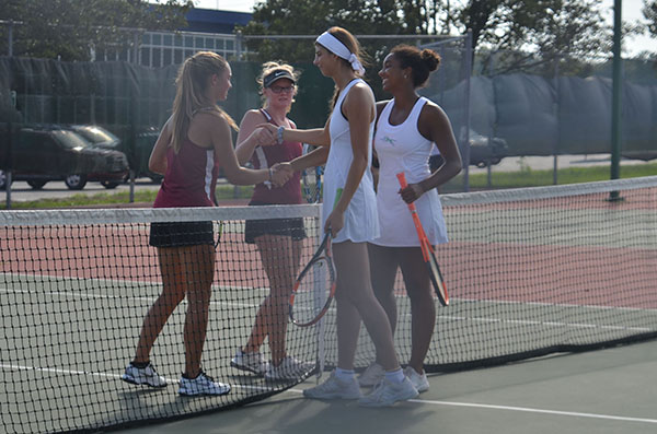 Khiara Cox, left and Jasmine Tucker,  right shake hands with their opponets after a home doubles match. Photo by Shyia Patrick