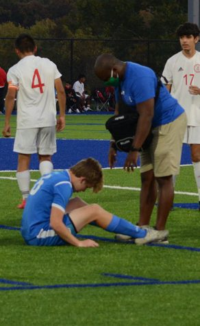 South trainer Andre Taylor tends to a South soccer player during a home match. Photo by Hailey Schinderling