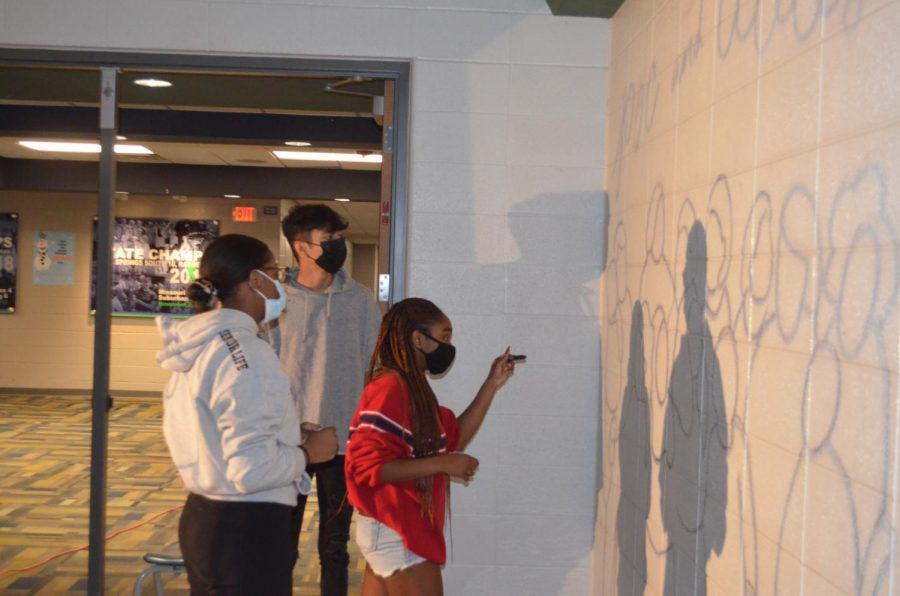 From left, South seniors MacKenzie Hammonds, Zain Mohammad, and Anaya Dewey work on a mural outside of the main gym. The three seniors are members of the People of Color and Allies club at South.